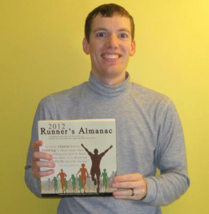 Blaine holding a proof of the 2012 Runner's Almanac